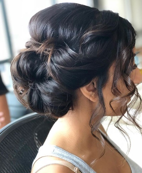 Wedding hairstyles for long hair: Brunette with her hair in a big bun updo with loose curly strands