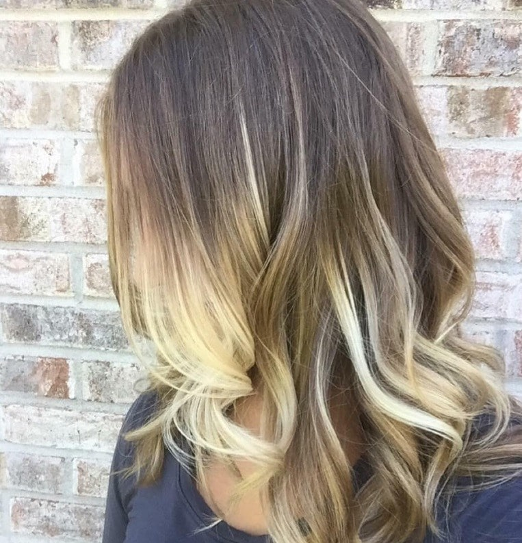 side shot of a woman with long wavy hair and light blonde highlights