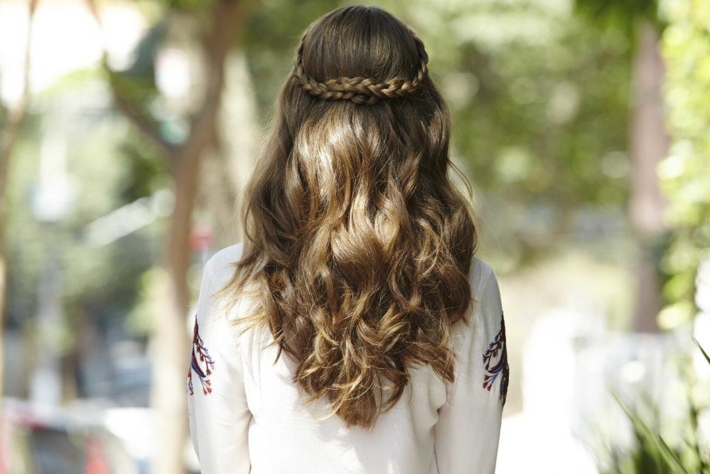festival braids: back shot of a woman with medium brown hair styled into a half-up, half-down braid, complete with beachy waves