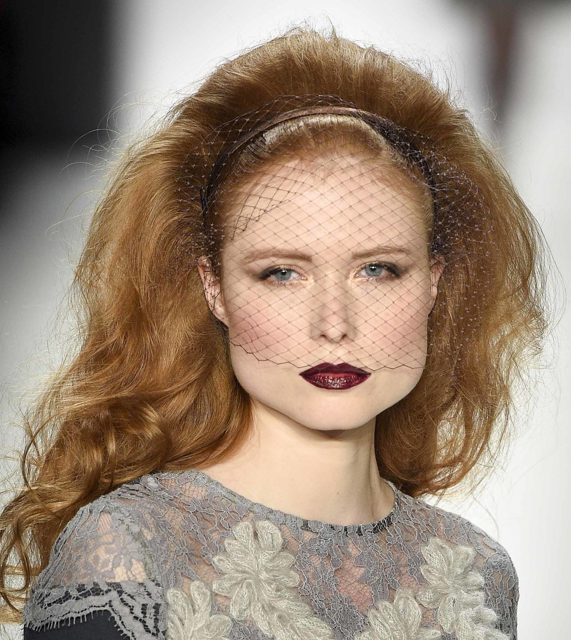 model with golden blonde curly hair in bouffant style wearing black net veil and grey lace floral pattern dress at aw16 fashion week in berlin