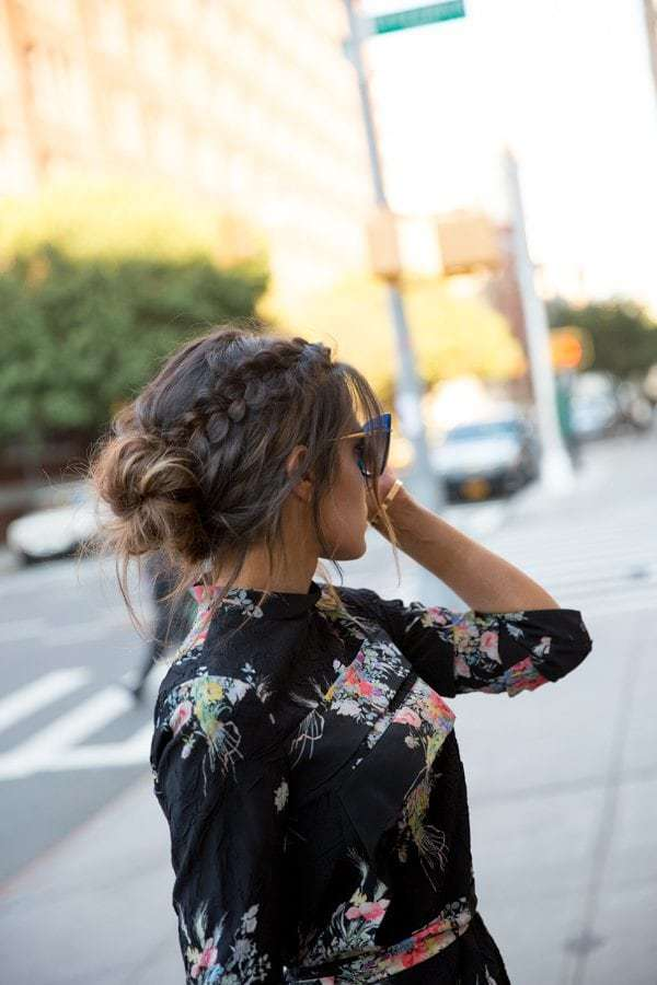 Braided hairstyles for thick hair: Woman with dark brown hair styled into a braided low messy bun, wearing floral dress and posing outside