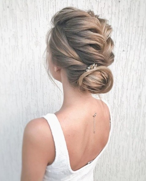 Wedding hairstyles for long hair: Woman with light brown/dark blonde hair in a French braid into a chignon bun