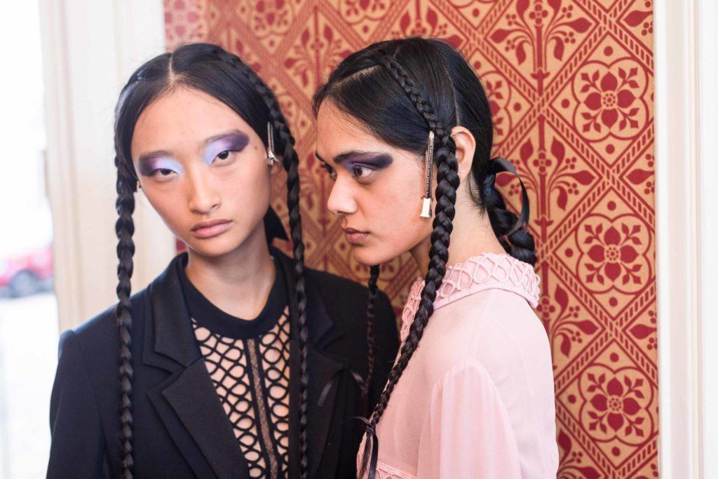 model with dark brown long hair in braided style wearing bold eye makeup at aw16 fashion week show