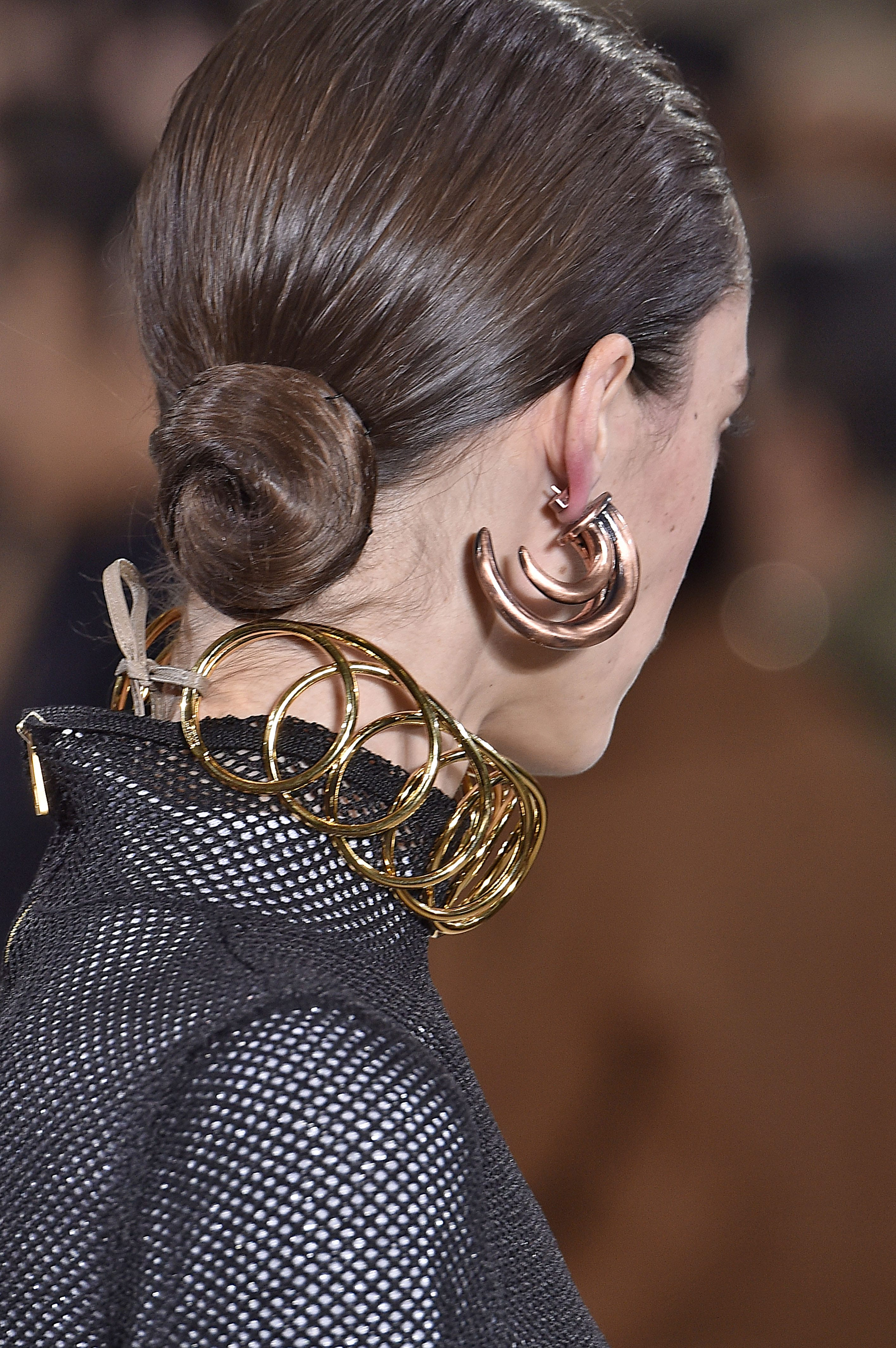 bun hairstyles: model with medium brown hair styled in a wet look low twisted bun hairstyle with large gold earrings and necklace