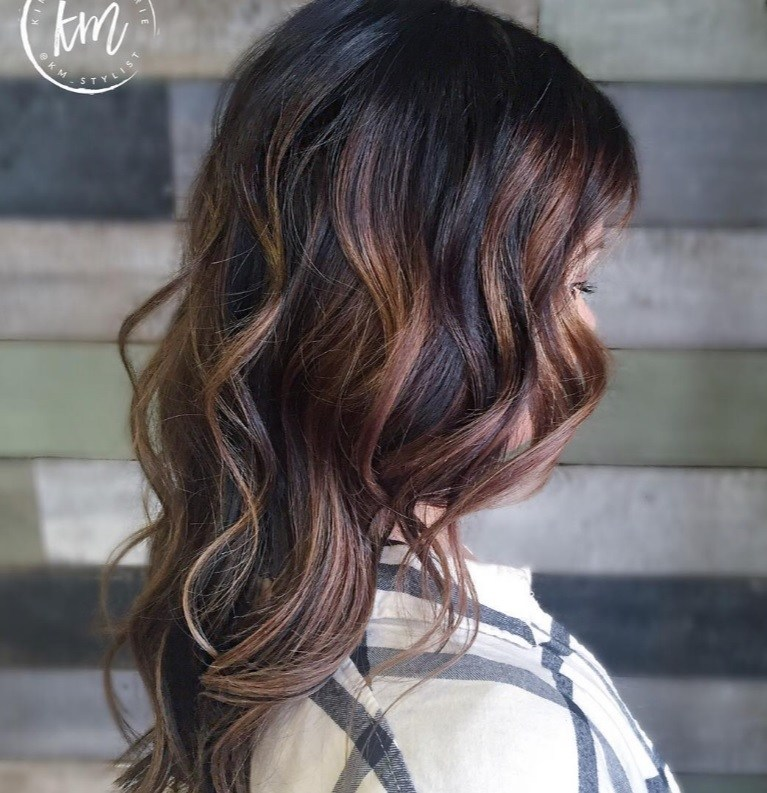 side shot of a woman with dark, long brown hair in waves and a cinnamon brown balayage