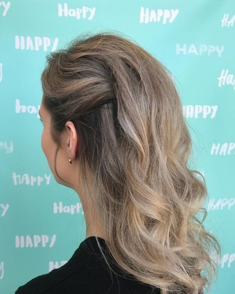 Wedding hairstyles for long hair: Woman with light brown hair in a half clipped up updo with curly lengths