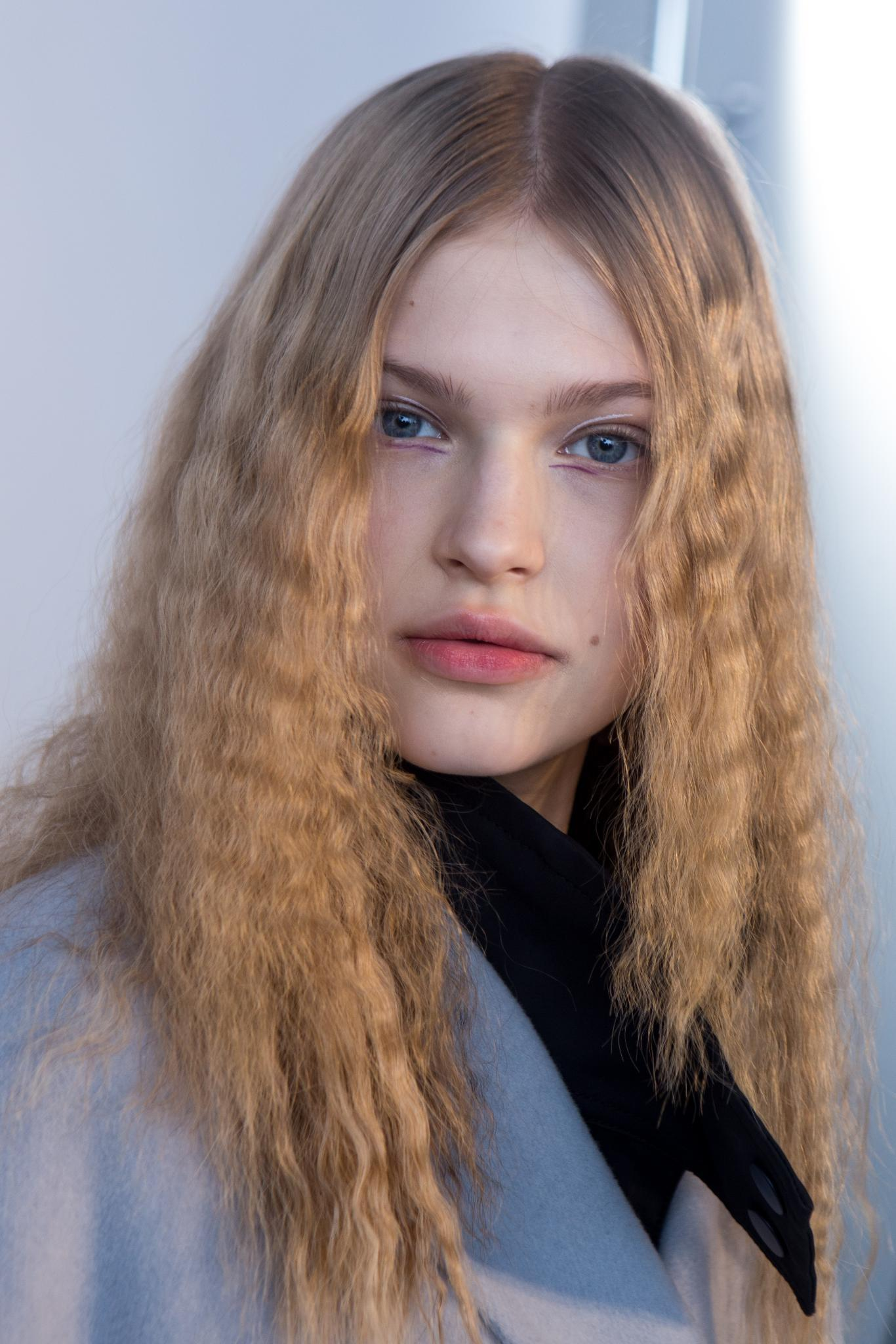 Hairstyles for thick hair: Model with natural blonde long thick hair crimped, wearing grey blazer with black turtleneck backstage