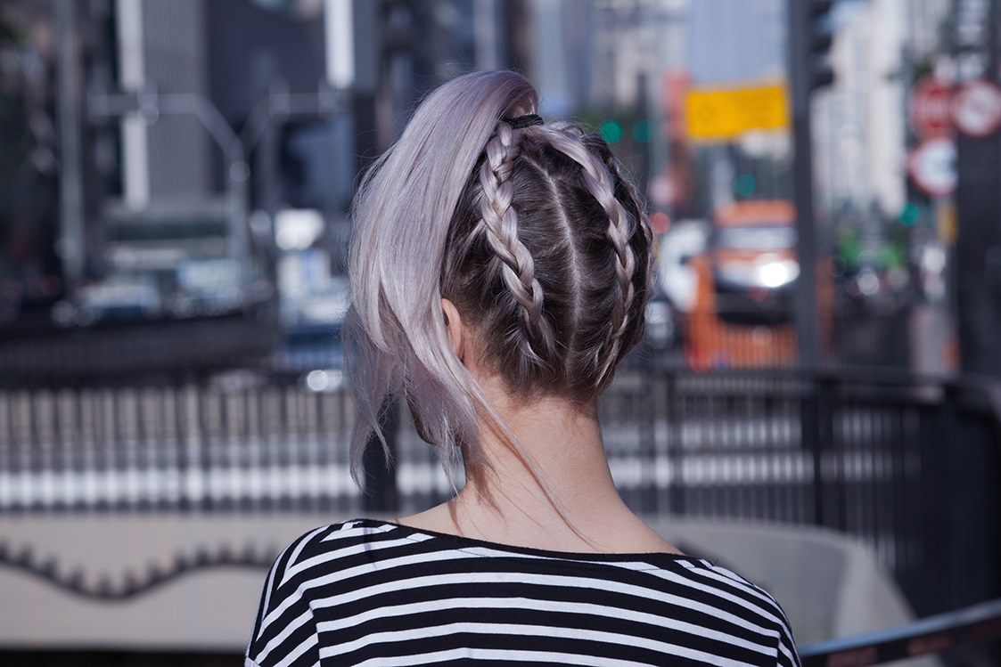 back view of woman with an upside down braided ponytail in lilac hair