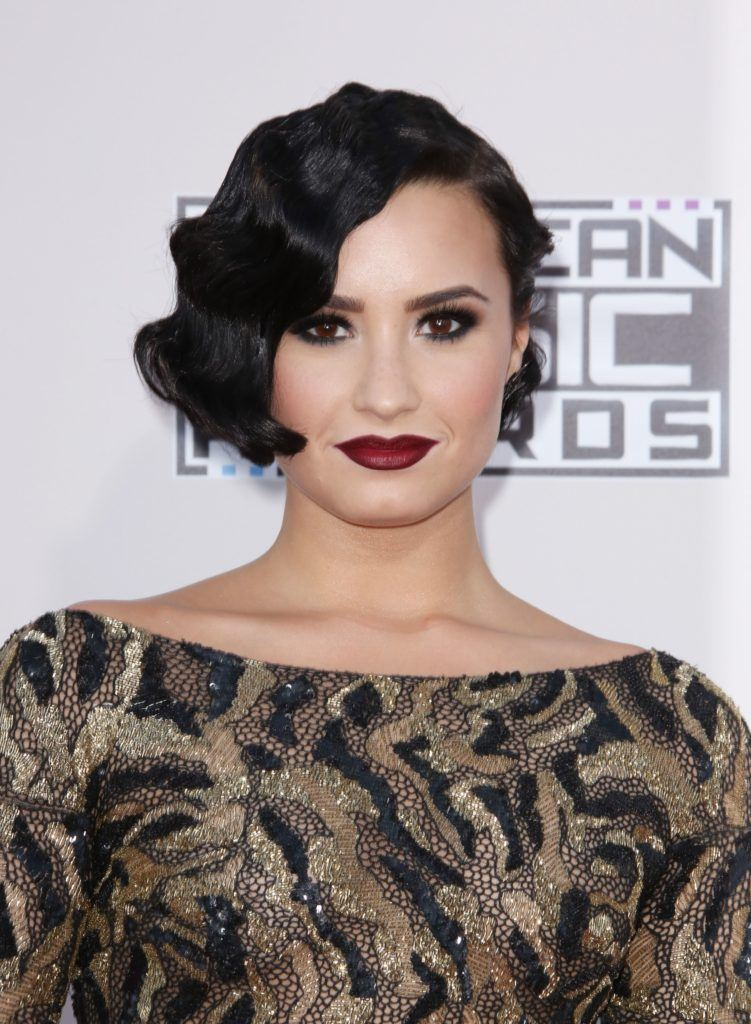 Vintage short hair: Close up shot of Demi Lovato with short dark brown hair styled into a finger waved wavy bob on the red carpet