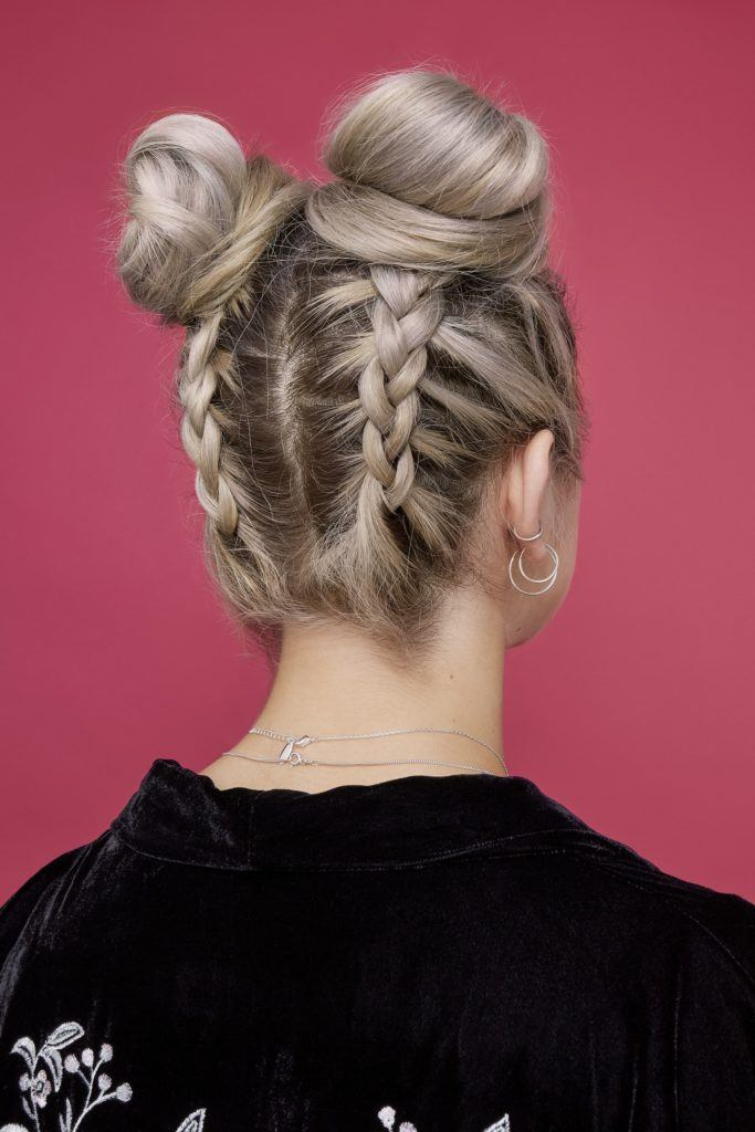 easy bun hairstyles: back view of blonde model with hair styled in two double braided space buns hairstyle