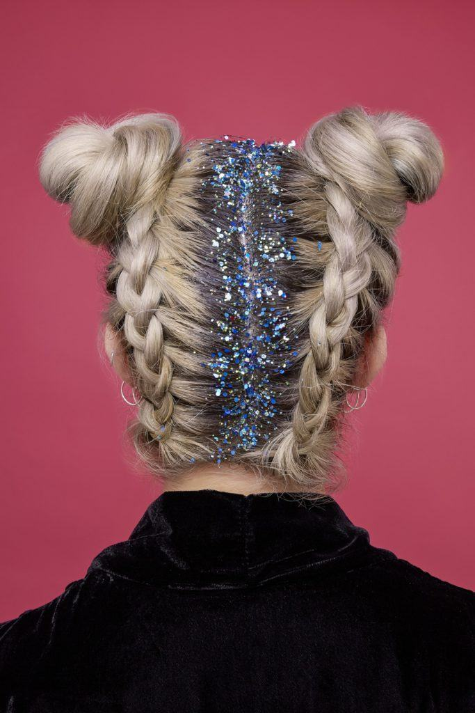 festival braids: back shot of woman with braided space buns, with glitter at the roots, wearing black top and pink background