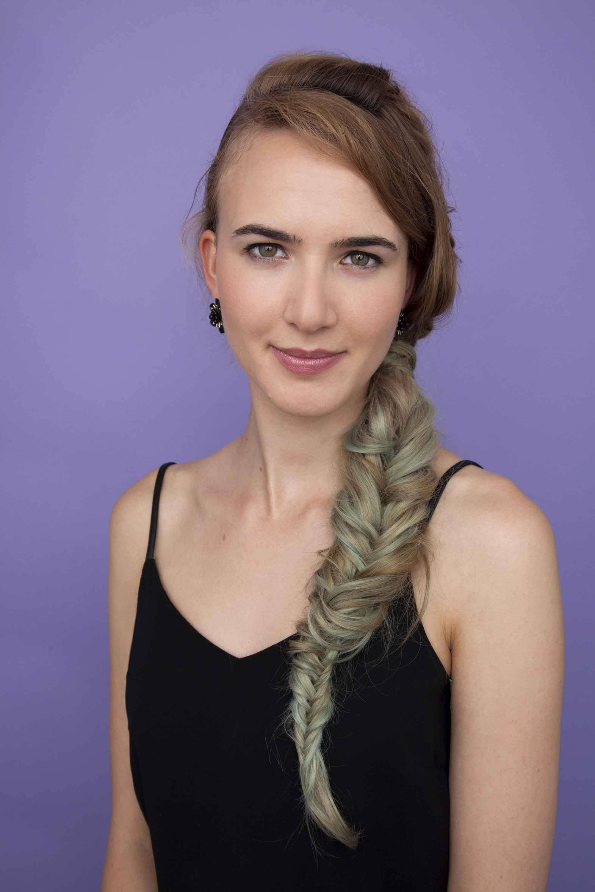 model with blue tinted blonde hair and a large fishtail plait against a purple background