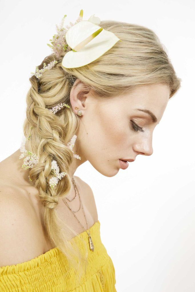 festival braids: close up shot of a model with a golden blonde messy fishtail worn to the side, complete with a lily flower and wearing a yellow bardot top