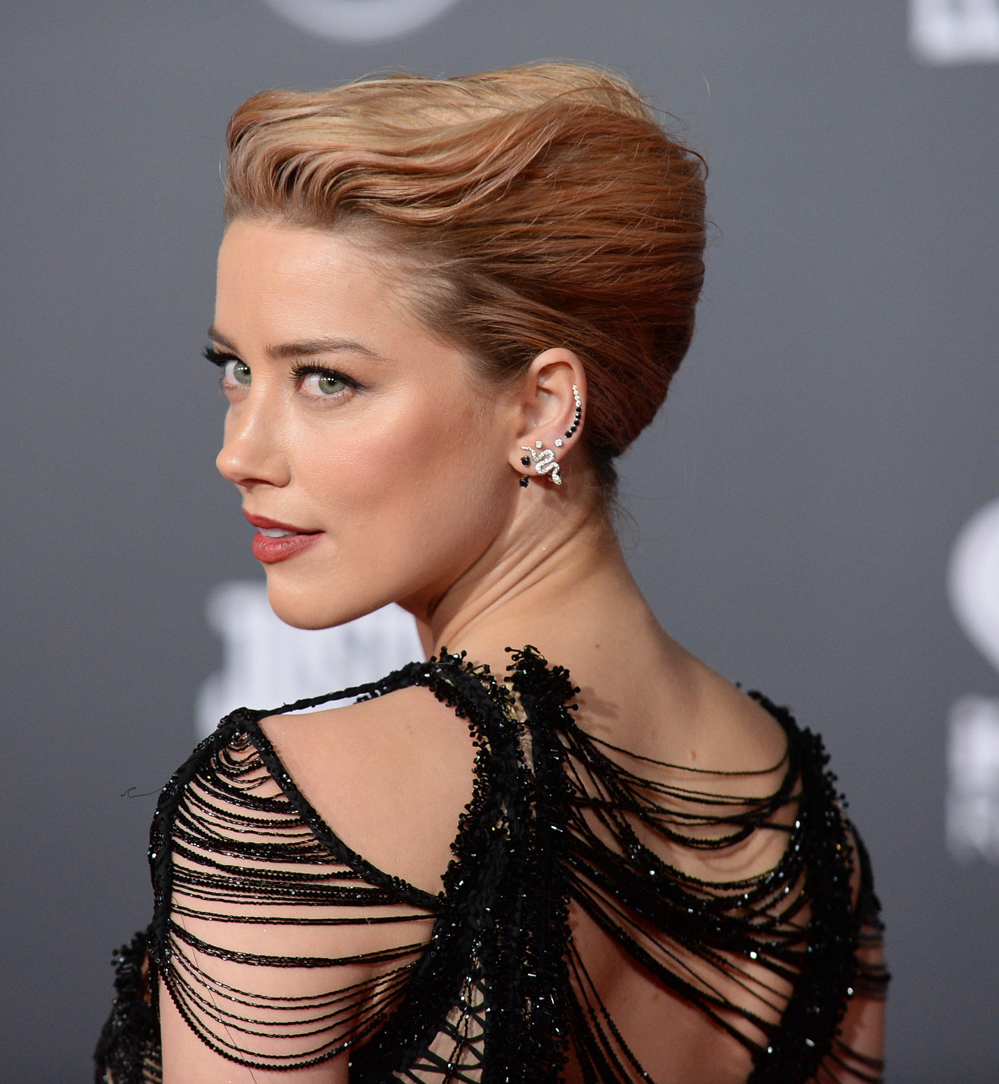 Vintage short hair: Close up side shot of Amber heard with a strawberry blonde, swept back French twist hairstyle on the red carpet