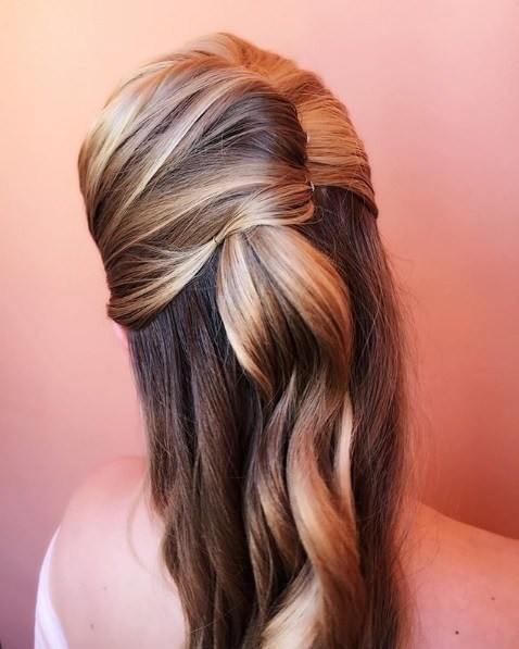 Wedding hairstyles for long hair: Back view of a woman with bronde hair in a curly half-up French twist