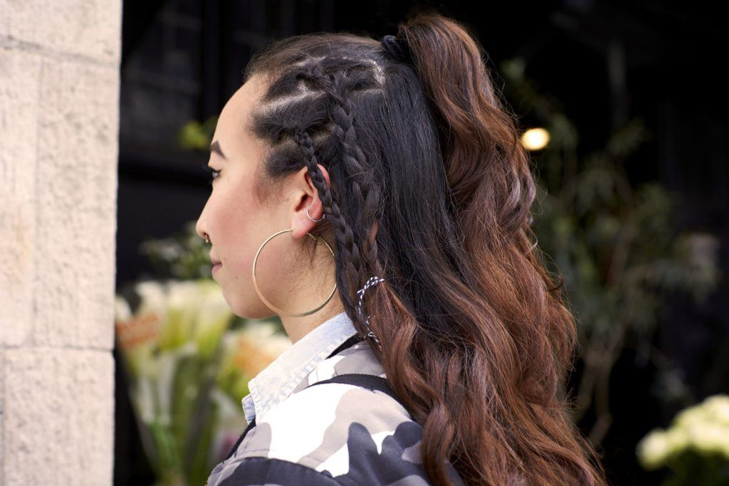 festival braids: close up side shot of a woman with dark brown hair styled into a half-up, half-down ponytail hairstyle, with hidden braids, wearing a floral top and posing on the street