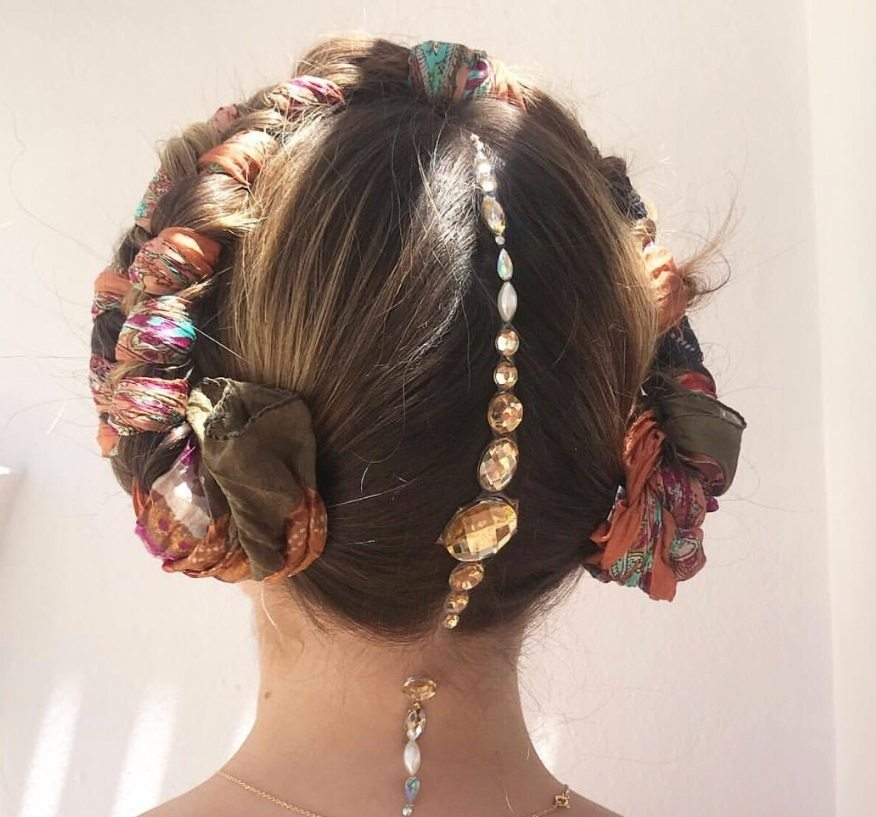 festival braids: close up back shot of model with a dark brown milkmaid braid with a headscarf woven through it, with an accessorised parting, posing against a white wall