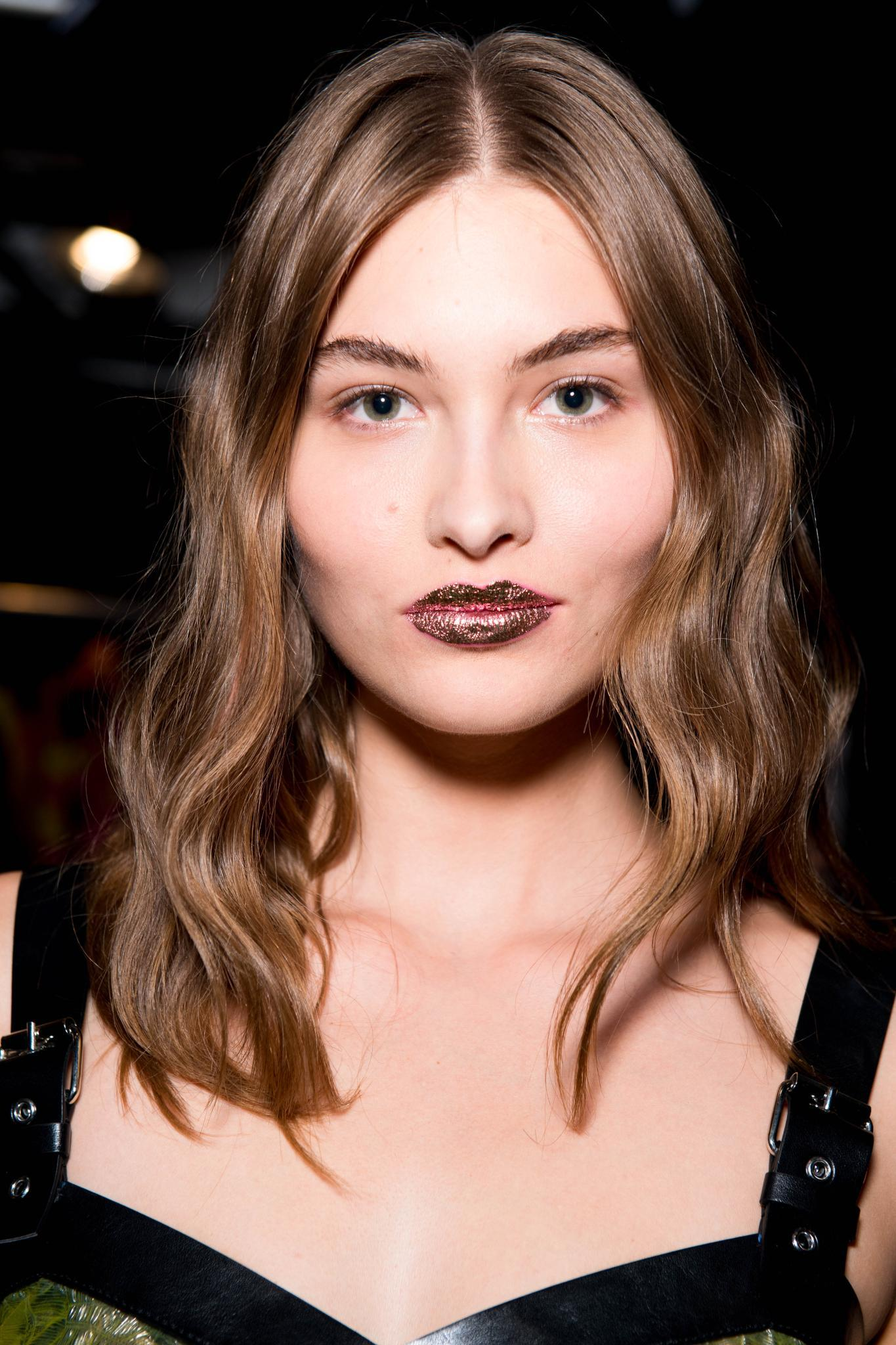 Hair glossing treatment: Woman with wavy shiny brown hair at Jermey Scott show with glitter lipstick