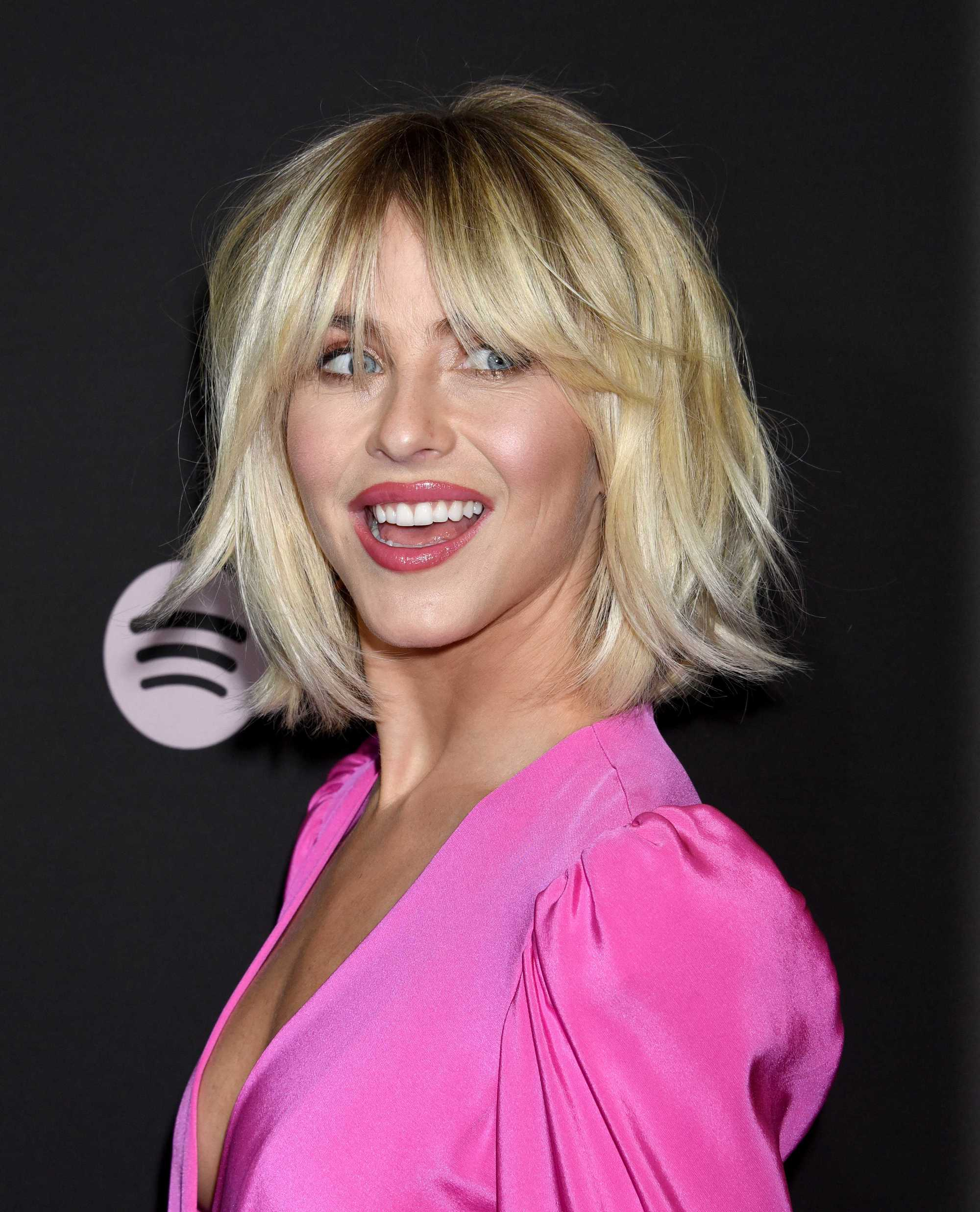 Thick hairstyles: Julianne Hough with short shaggy thick bob, wearing bright pink top and posing