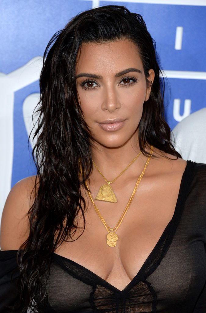 Kim Kardashian on the red carpet at the VMAs wearing a sheer black outfit and gold necklaces with her long dark brown hair worn in waves and a wet look style
