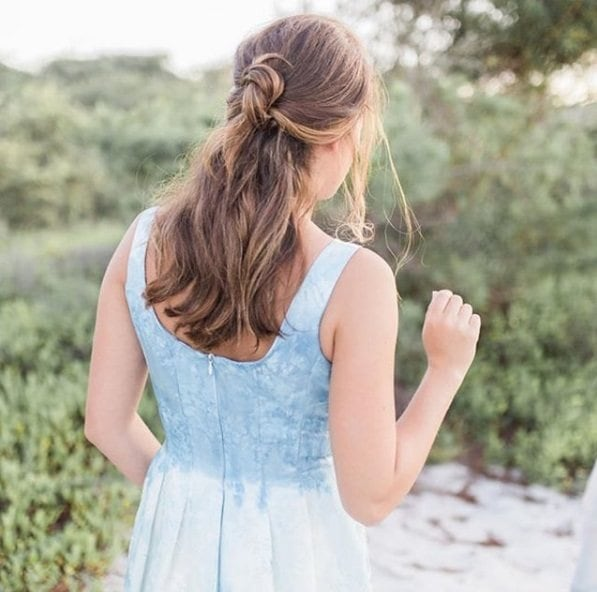 Wedding hairstyles for long hair: Back view of a woman with medium-long curly light brown hair in a half-up half-down knot hairstyle