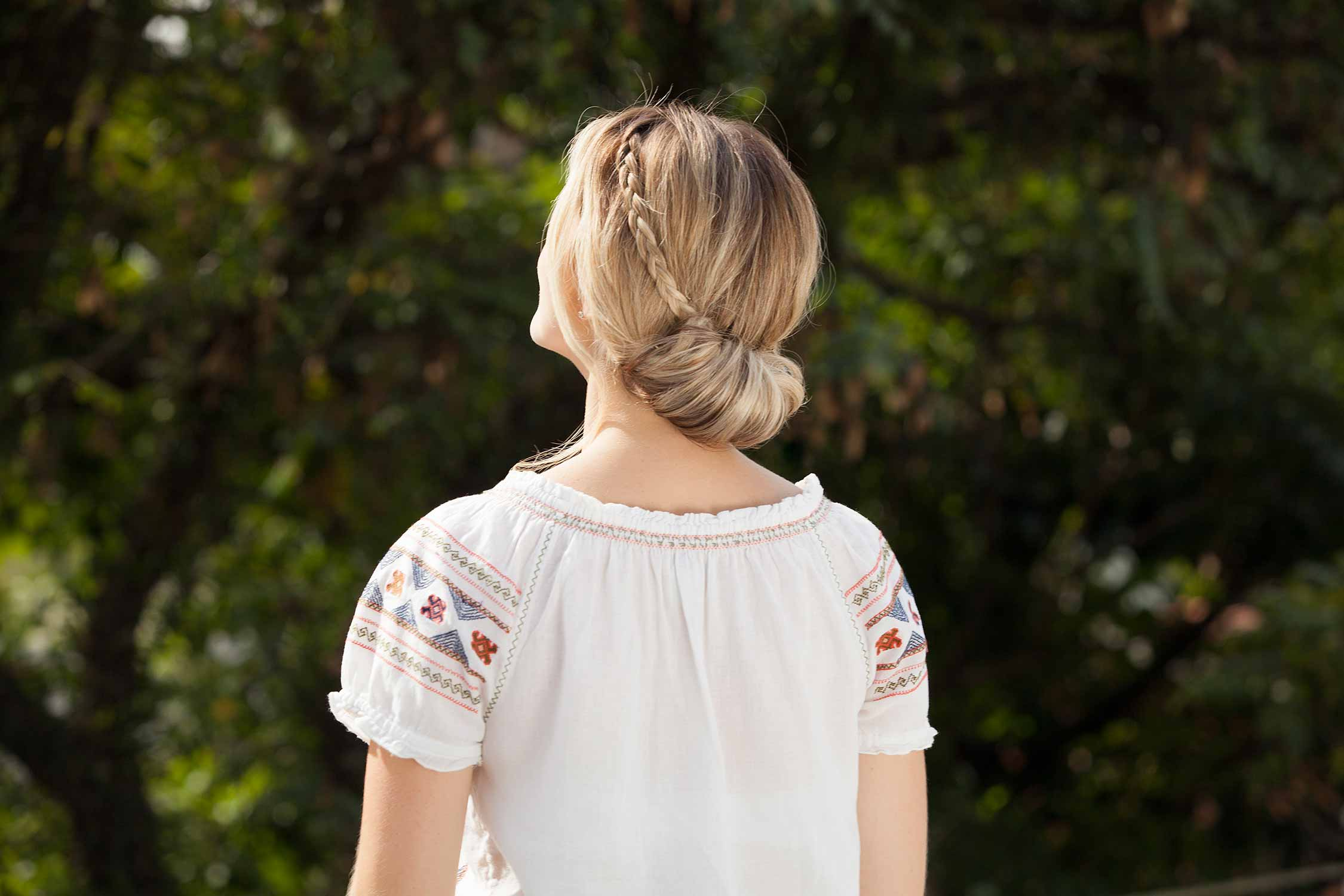 back view of woman with a low chignon bun and small braid in blonde hair