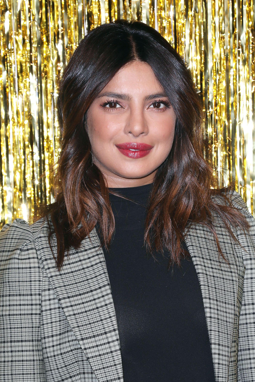 Hairstyles for thick hair: Priyanka Chopra with medium layered hair, wearing blazer with black top at a fashion show