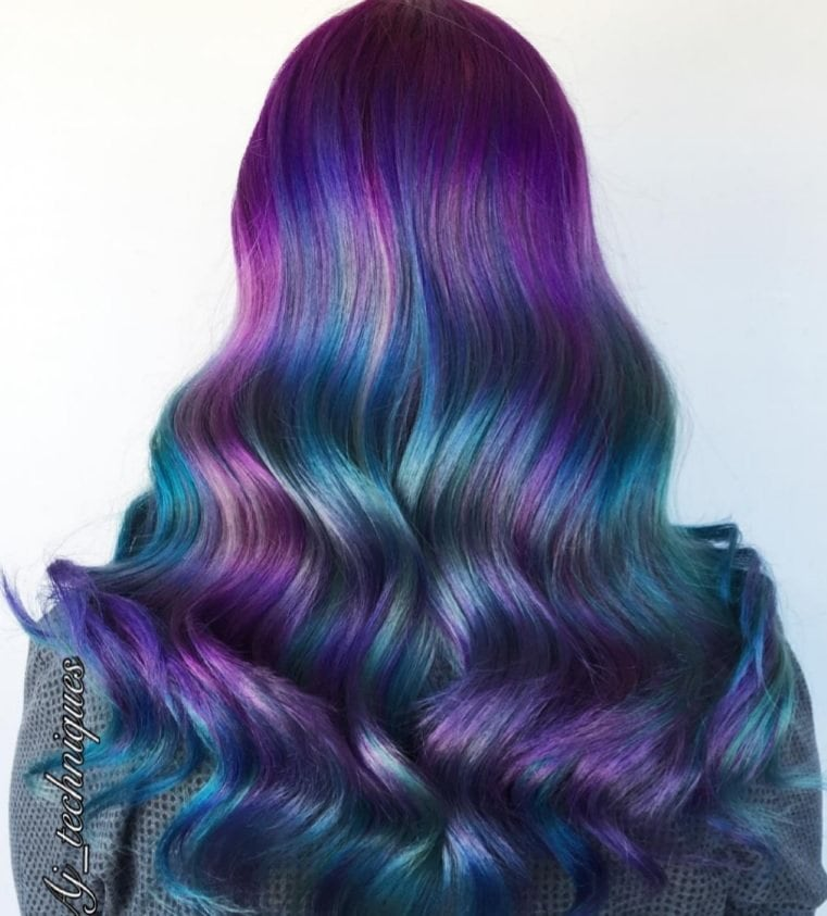 back shot of a woman with long hair in a bright blue and purple balayage colour