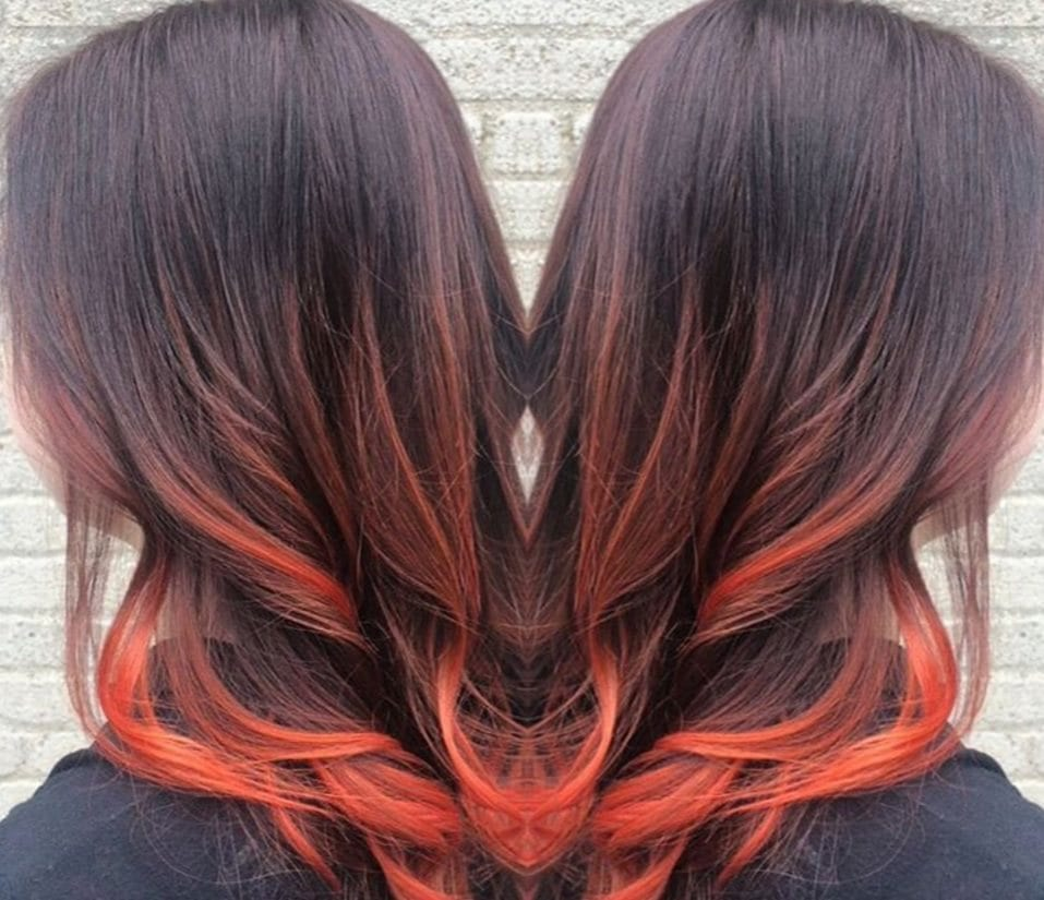 side shot of a woman with dark long hair in an orange balayage colour
