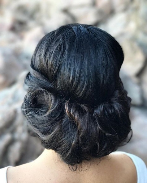 Wedding hairstyles for long hair: Back view of a woman with dark brown almost black hair in a low pinned updo style