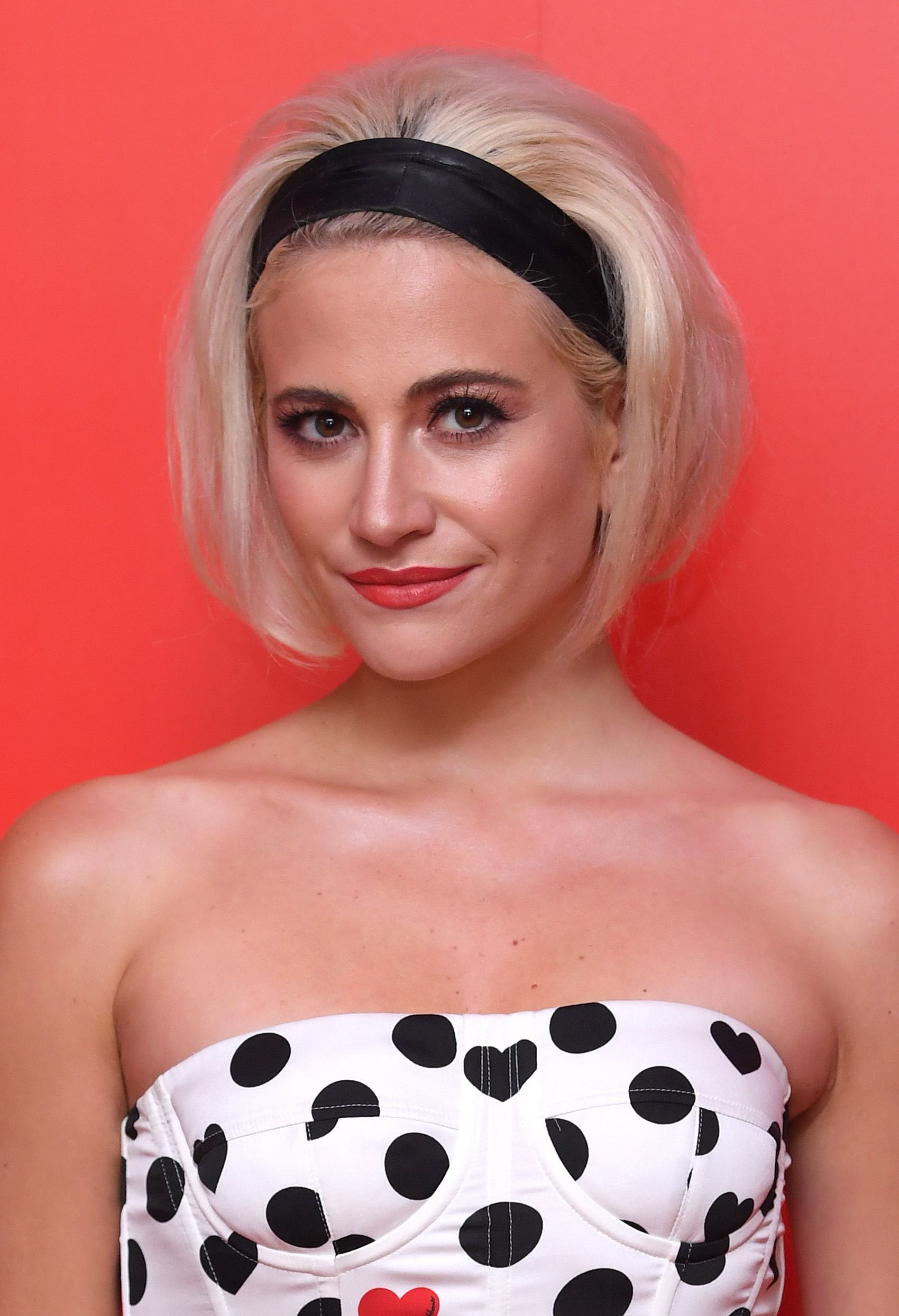 Vintage short hair: Close up shot of Pixie Lott with short bleach blonde hair styled into a bouffant with a headband