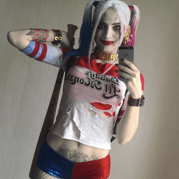 woman dressed as Harley Quinn with spray painted hair and pigtails