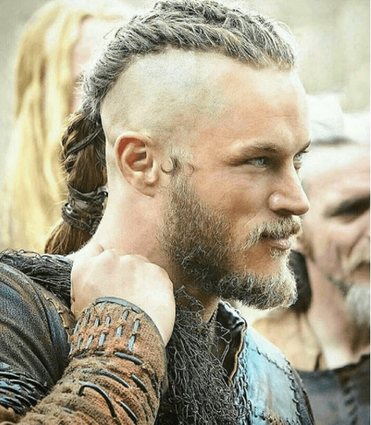 side view of Travis Fimmel with shaved head, braids and a beard filing Vikings