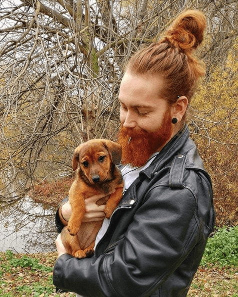 front view of a man with red hair in a top knot with a full beard holding a puppy