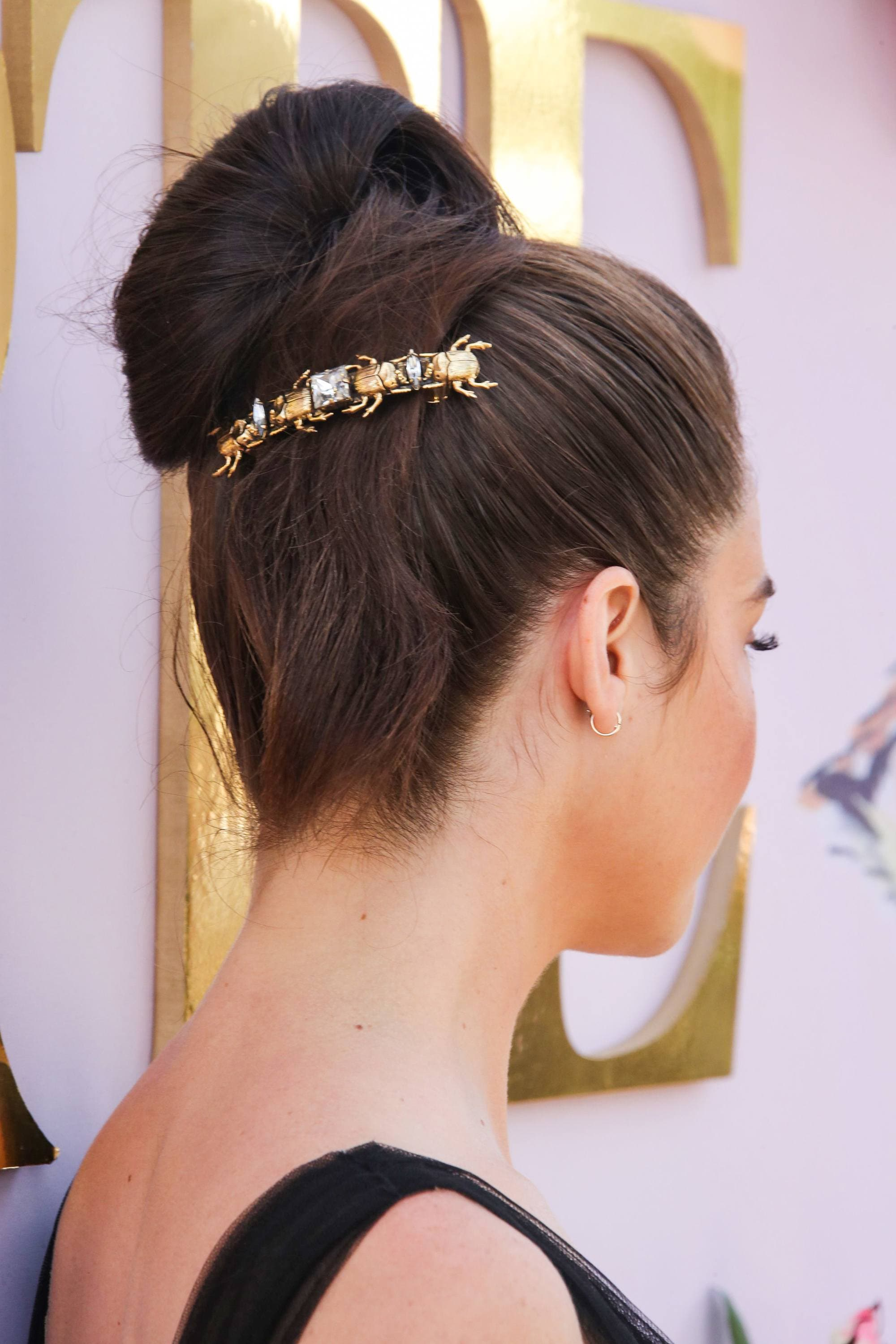 Thick hairstyles: Back shot of woman with smooth thick hair styled into a ballerina bun with barrette