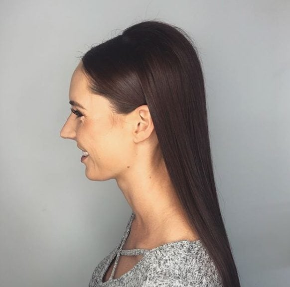 Wedding hairstyles for long hair: Side view of a woman with straight long dark hair with a bouffant