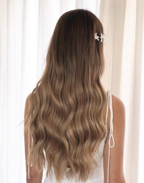 Wedding hairstyles for long hair: Back view of a woman with soft ash brown hair in subtle waves with a sparkly barrette