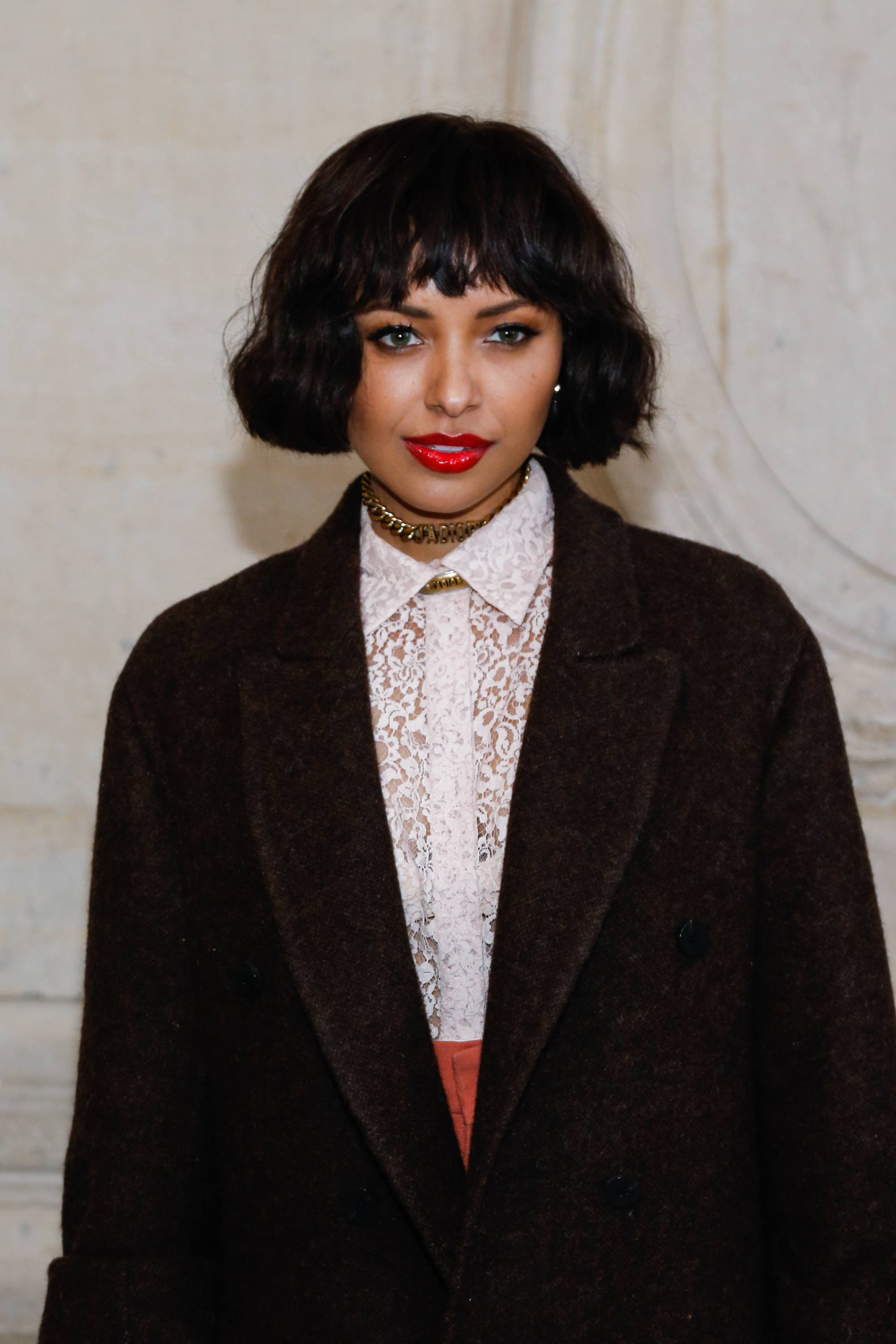 Thick hairstyles: Kat Graham with short thick wavy hair with wispy bangs, wearing black blazer with white shirt