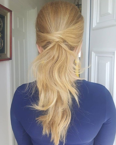 Wedding hairstyles for long hair: Back view of a blonde woman with her hair in a wrapped textured low ponytail