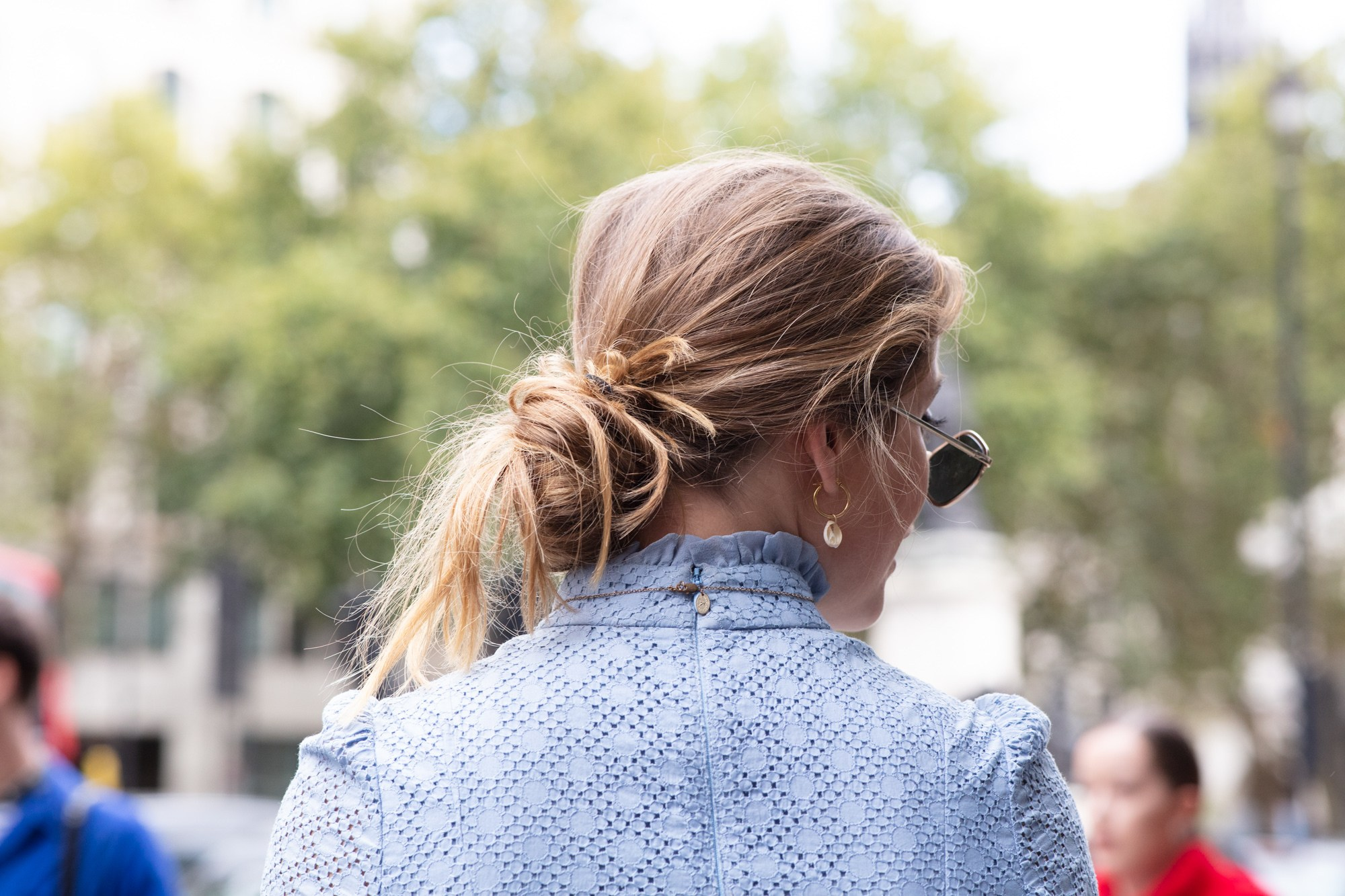 Hairstyles for thick hair: Woman with dirty blonde hair styled into a messy low bun wearing blue polka dot dress