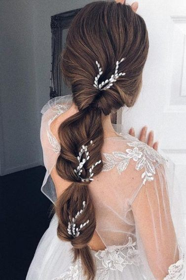 Wedding hairstyles for long hair: Back view of a brunette woman with waist-length hair in a bridal topsy turvy ponytail style