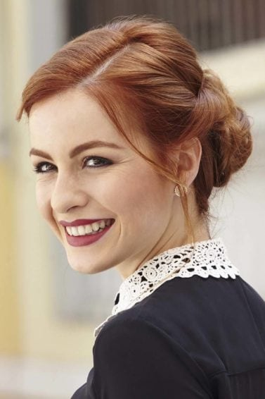 Happy redhead with twist updo hairstyle