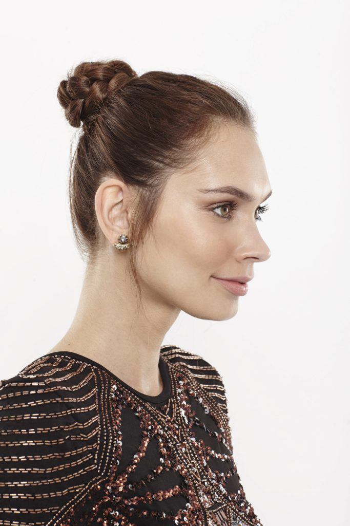 bun hairstyles: side view of model with brown hair styled in a high braided bun hairstyle updo
