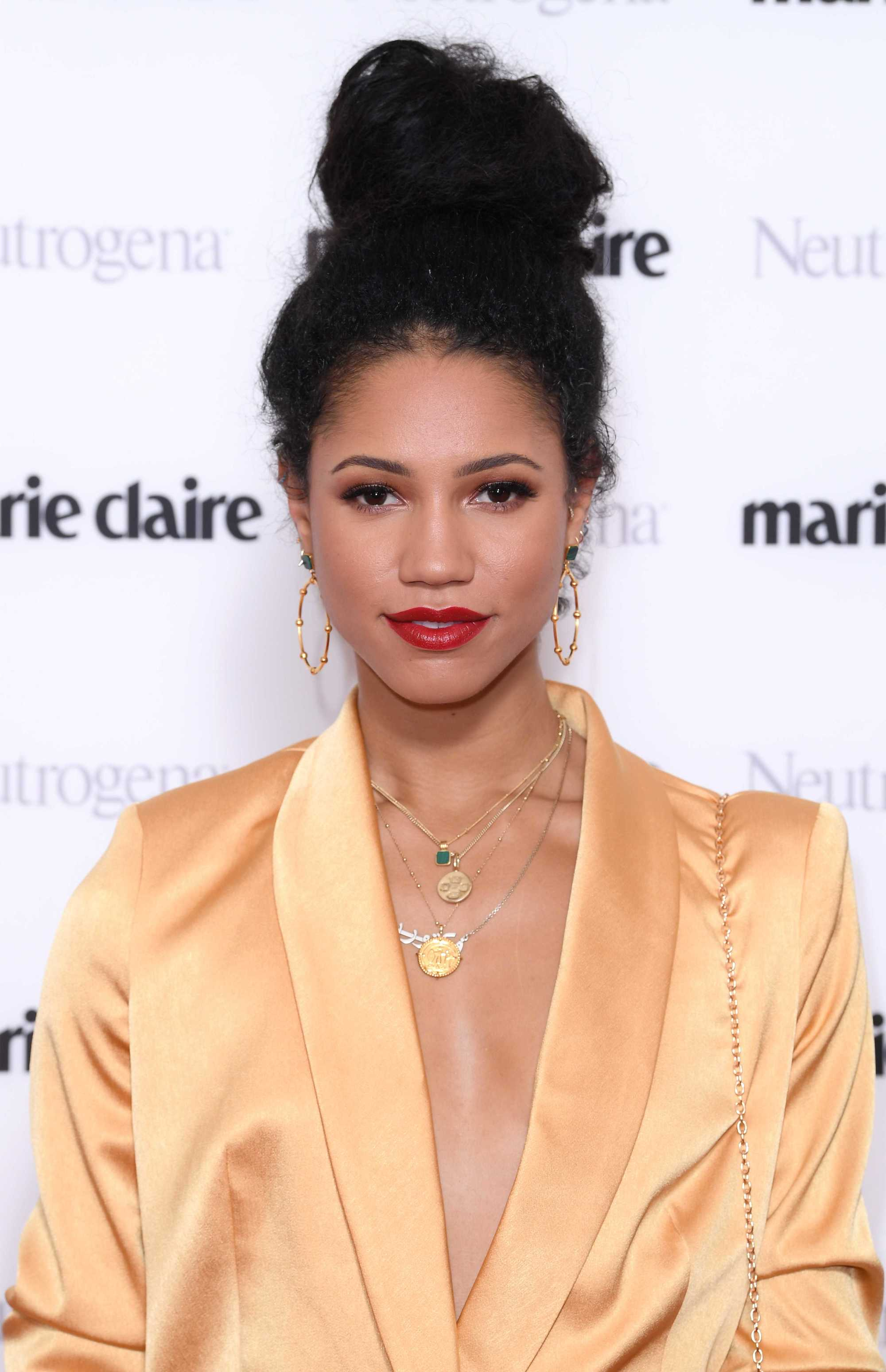 Hairstyles for thick hair: Vick Hope with her natural brown thick hair styled into a high bun