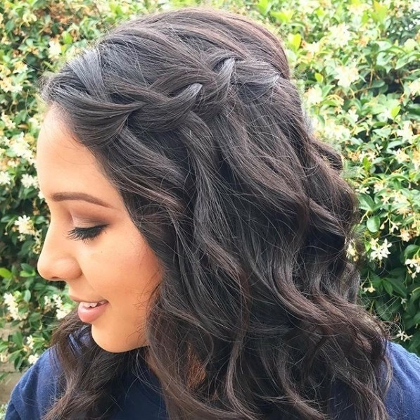 Wedding hairstyles for long hair: Close-up shot of a woman with curled dark hair in a waterfall braid