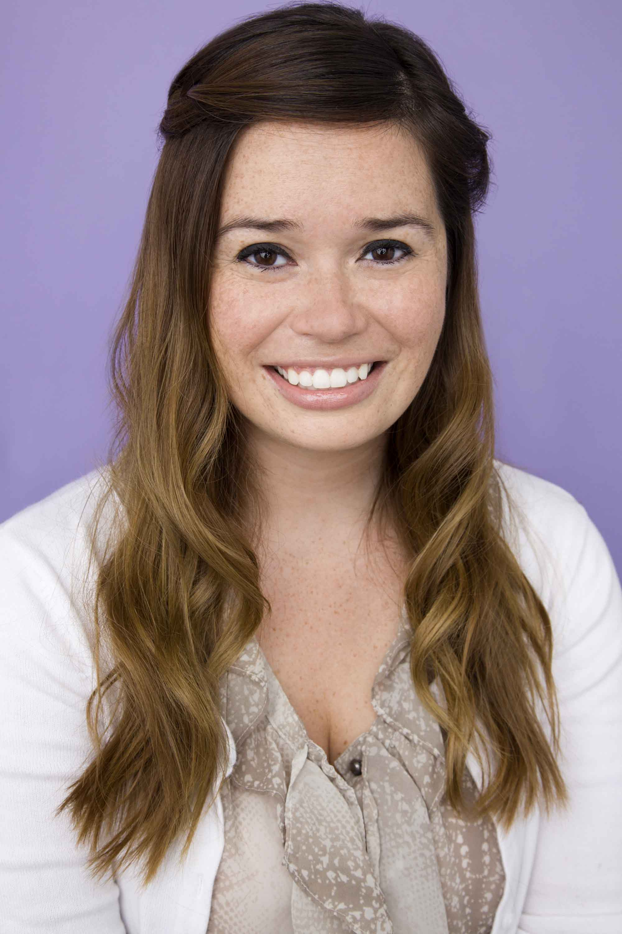 model with brunette hair and a set of soft waves against a purple background