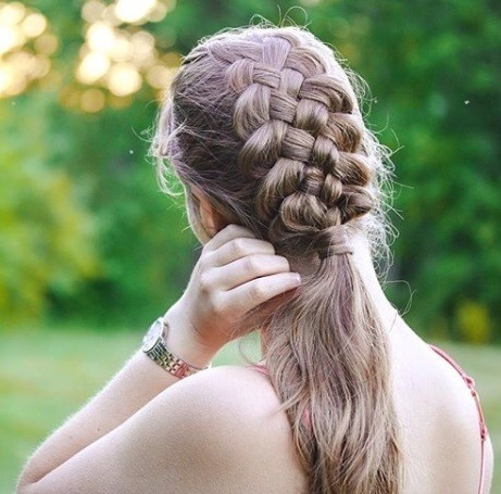 Outdoor shot of a woman with light brown hair in a 5 strand Dutch braid ponytail hairstyle