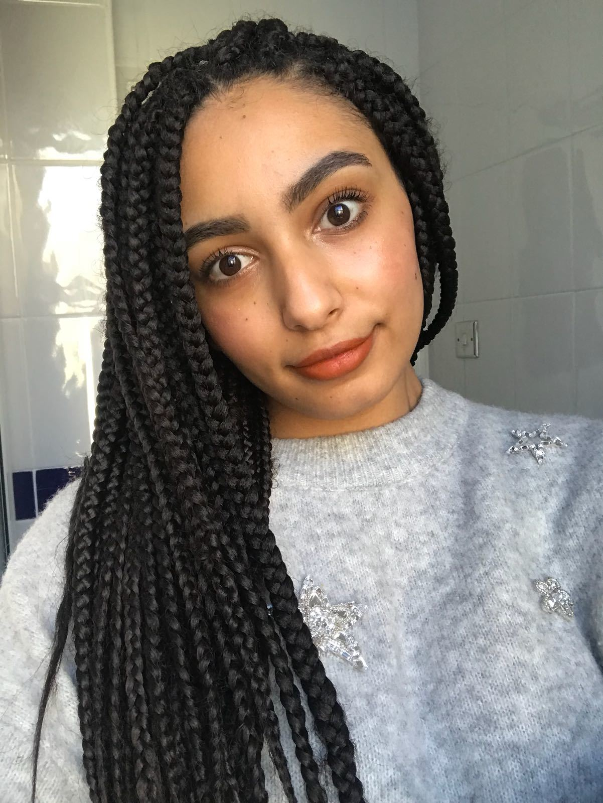 close up shot of woman with long box braids swept to the side, wearing grey jumper and posing