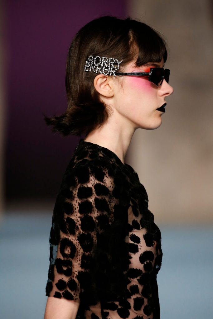 "brunette model at ashley williams aw18 show with ""sorry error"" hairclip wearing a black spotted outfit"