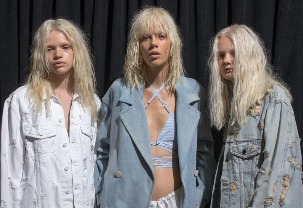 3 blonde models with shaggy hair bleached white wearing blue and white denim outfits